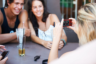 Buy stock photo Group of teens enjoying beverages while at an outdoor restaurant while taking a photo with a mobile phone