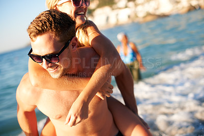 Buy stock photo Teen girl getting a piggyback from her boyfriend while on the beach