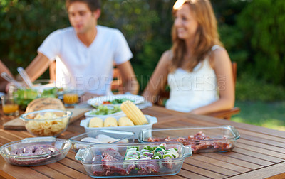 Buy stock photo Smiling teen couple sharing a healthy lunch together - focus on the foreground