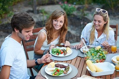 Buy stock photo Smiling young people at a lunch with a group of friends