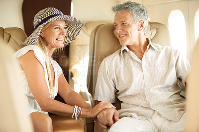 Buy stock photo Smiling senior couple holding hands on an airplane heading overseas