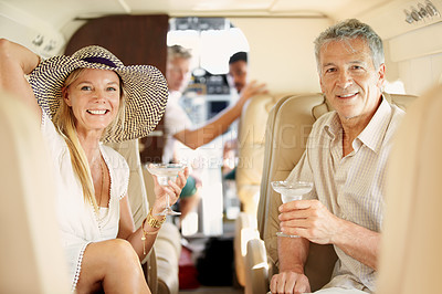 Buy stock photo Shot of a mature couple sitting in the back of a private jet drinking cocktails