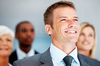 Buy stock photo Closeup of handsome business man with multi ethic team in background