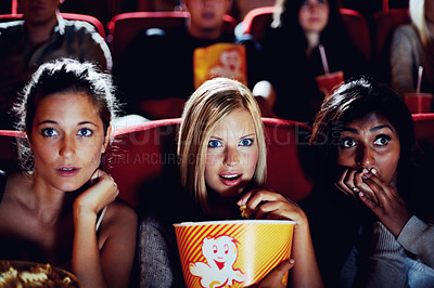 Buy stock photo Three girlfriends sitting close together looking afraid and nervous in a movie theatre