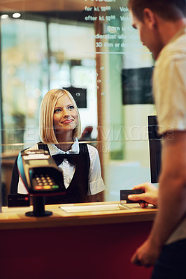 Buy stock photo A beautiful woman dressed in uniform sitting in a ticket booth serving a male customer
