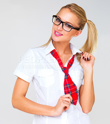 Buy stock photo Studio shot of a beautiful young woman in a school uniform against a gray background