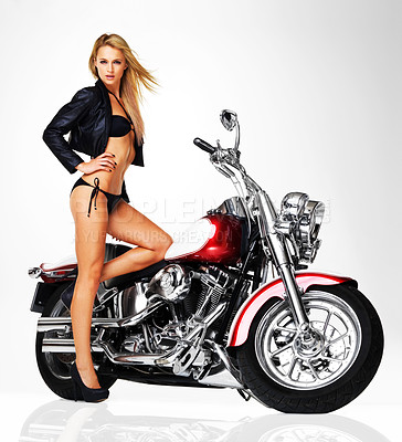 Buy stock photo Studio portrait of a sexy young woman in a leather jacket and bikini standing next to a motorbike