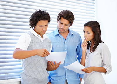 Buy stock photo A group of businesspeople holding a discussion over documents