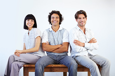 Buy stock photo Three casual entrepreneurs sitting on a bench together