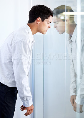 Buy stock photo A young businessman hitting his head against a glass door with a look of defeat on his face
