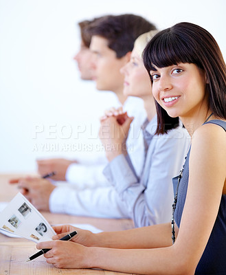 Buy stock photo Portrait of a pretty businesswoman smiling - blurred colleagues in the background