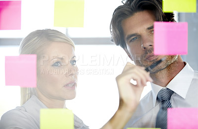 Buy stock photo A man and woman in the office looking at notes on a glass window, discussing and deciding