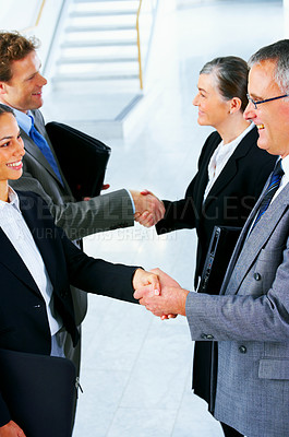 Buy stock photo Handshake and teamwork. Four businesspeople shanking hands in a light and modern office.