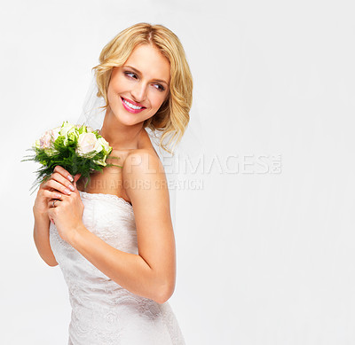 Buy stock photo Young bride holding her bouquet with a sweet smile