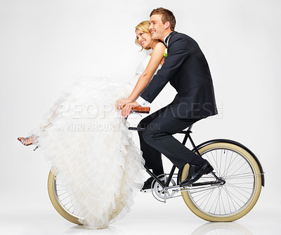 Buy stock photo Studio shot of a newlywed couple riding an old bicycle