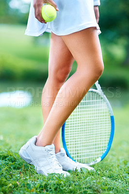 Buy stock photo Cropped view of the legs of a female tennis player with her racquet and ball