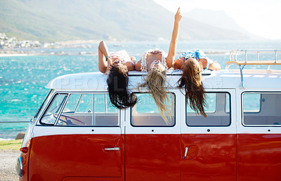 Buy stock photo Three young girls bonding and sharing stories on top of their mini van by the sea