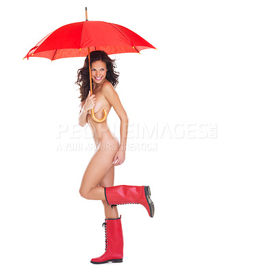 Buy stock photo Studio portrait of a cute young nude woman holding a red umbrella and wearing gumboots while standing against a white background