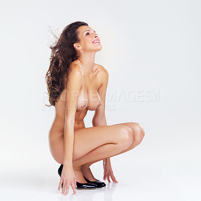 Buy stock photo Studio shot of a beautiful young nude woman crouched on the floor wearing stilettos against a white background