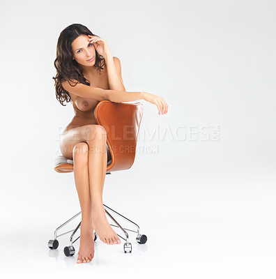 Buy stock photo Studio portrait of an attractive young nude woman sitting on a office chair against a white background