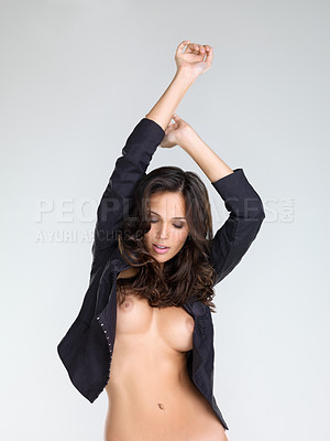 Buy stock photo Studio portrait of a gorgeous young nude woman dancing while standing against a grey background