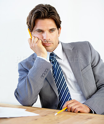 Buy stock photo Bored young businessman sitting at his desk
