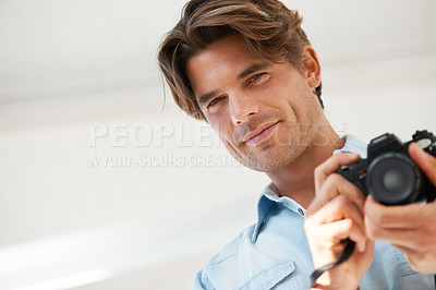Buy stock photo Portrait of a young photographer holding a DSLR