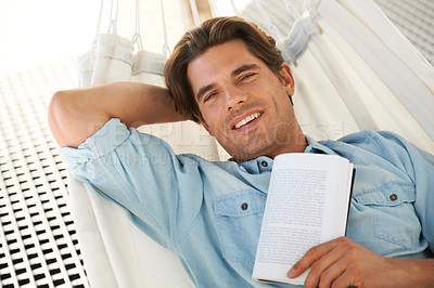 Buy stock photo Portrait of a young man relaxing with a book while lying on a hammock