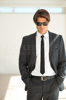 Buy stock photo Portrait of a handsome young businessman in a suit and wearing sunglasses