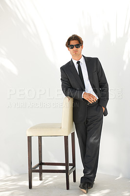 Buy stock photo Full-length portrait of a businessman in a suit and sunglasses leaning on a chair