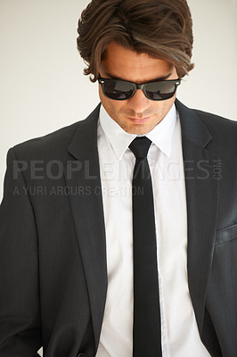 Buy stock photo A handsome young businessman in a suit and wearing sunglasses