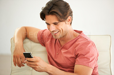 Buy stock photo A handsome young man reading a text message on his phone