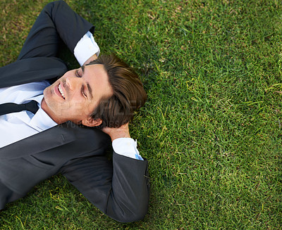 Buy stock photo A young businessman lying down on green grass