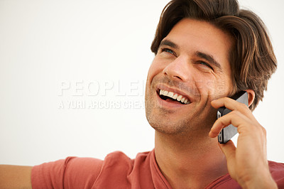 Buy stock photo A handsome young man talking to someone on his cellphone