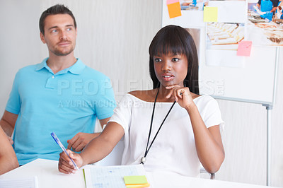 Buy stock photo Cropped shot of a young businesswoman looking thoughtful while sitting around a table with her colleagues