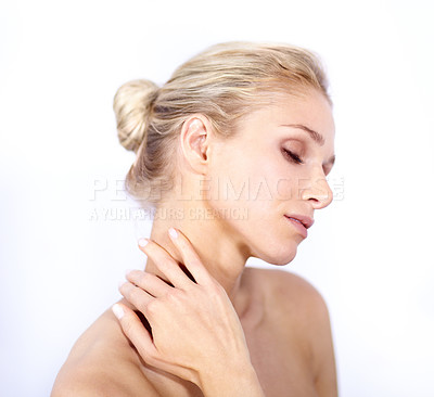 Buy stock photo Young woman caressing her neck while isolated on white