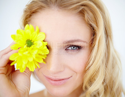 Buy stock photo Closeup portrait of a pretty young woman holding a yellow daisy over her eye