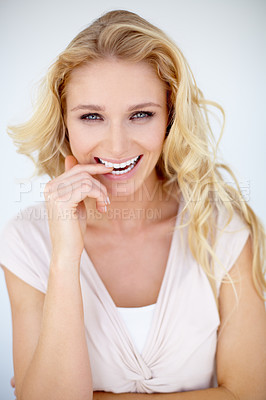 Buy stock photo Pretty young woman biting her finger in a flirty manner