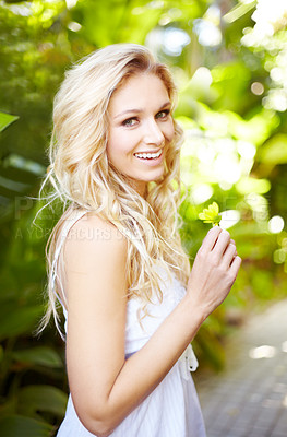 Buy stock photo Portrait of a pretty young woman standing outdoors while holding a daisy