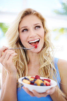 Buy stock photo Pretty young woman looking up as she eats her fruit salad