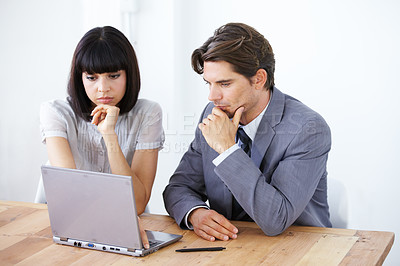 Buy stock photo Two young executives working on a laptop together