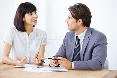 Buy stock photo Two young businesspeople having a lively conversation at the office