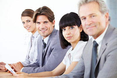 Buy stock photo Portrait of a young handsome executive sitting with his business team