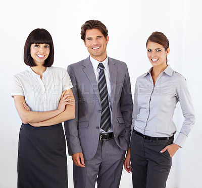 Buy stock photo Portrait of three young, ambitious executives standing together and smiling confidently