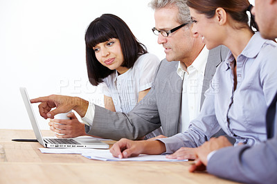 Buy stock photo Four enterprising executives strategizing on a laptop together