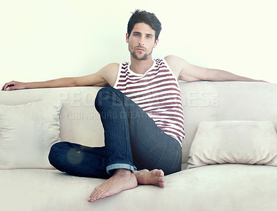 Buy stock photo Portrait of a carefree young male relaxing on a sofa  wearing casual jeans and a vest