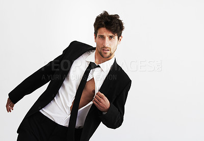 Buy stock photo Portrait of a sexy young man pulling open his unbuttoned shirt wearing a smart balck suit and tie - Copyspace