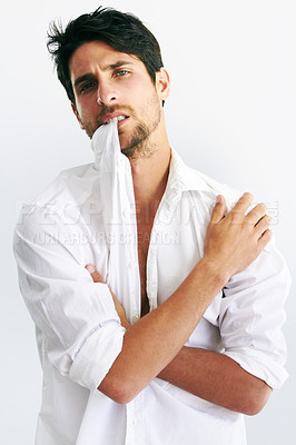Buy stock photo Portrait of a handsome male biting the collar of his white shirt