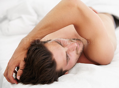 Buy stock photo A young male with his arm raised over his head waking up in the morning