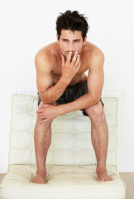 Buy stock photo Portrait of a handsome young male thinking while sitting on top of a small sofa in a pair of shorts